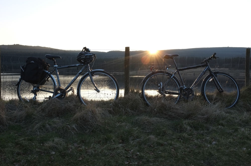 Touring bikes propped up against a wire fence, in front of the sun, setting behind Kielder Water.
